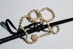 White pearls on black leather. Strand of white woman's pearls wrapped around a black leather riding crop on white Stock Photos