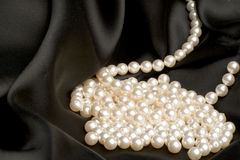 White pearls on a black satin Royalty Free Stock Photo