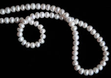 White pearls on the black silk as background Royalty Free Stock Photo