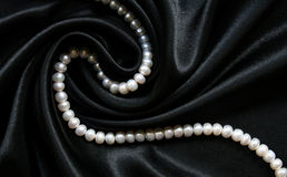 White pearls on the black silk as background Stock Photo