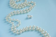 White pearls on blue background - luxury fashion concept. Space for text Royalty Free Stock Image