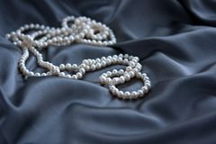 White pearls on blue satin. Beautiful white pearls on blue satin,  background Royalty Free Stock Images
