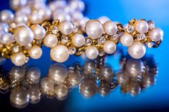 White pearls collier isolated on black blue. Background royalty free stock image