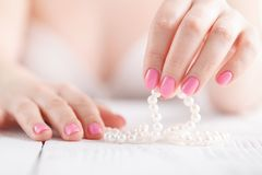 White pearls in female hands,with nails painted pink. White pearls in female hands, with nails painted pink Royalty Free Stock Images
