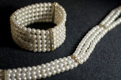 White pearls jewelry. Pearl jewelry on dark grey background royalty free stock image