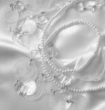 White pearls and nacreous beeds on white silk or satin as weddin Royalty Free Stock Photo