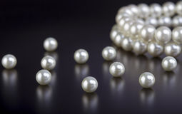 White pearls necklace on black Stock Photos