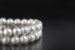 White pearls necklace on black Stock Images