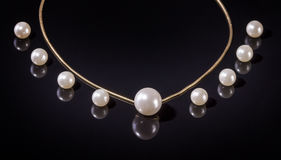 White pearls necklace on black background Stock Images