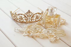 White pearls necklace, diamond tiara and perfume bottle. On white toilette table. Selective focus Royalty Free Stock Photography