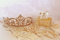 White pearls necklace, diamond tiara and perfume bottle. On white toilette table. Selective focus Royalty Free Stock Image