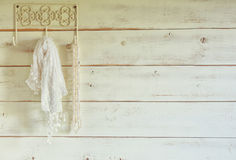 White pearls necklace and lace scarf hanging on wooden wall. vintage filtered. selective focus. Royalty Free Stock Image