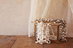White pearls necklace on old wooden table Royalty Free Stock Photo