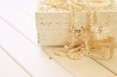 White pearls necklace and perfume bottle on toilette table Royalty Free Stock Photo