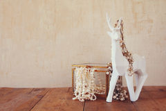 White pearls necklace and white deer on wooden table Stock Images