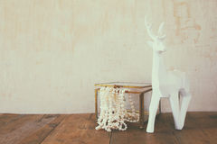 White pearls necklace and white deer on wooden table Stock Photography