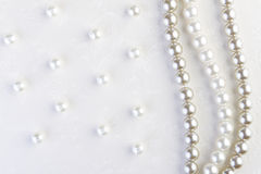 White pearls necklace on white paper Stock Images