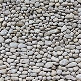 White pebble wall background - nature concept. Wall made of small white sea pebbles - natural texture background stock image