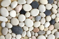 White pebbles background, simplicity, daylight, stones. Mix colors pebbles background, simplicity, daylight, stones, spread on wooden background, one by one Royalty Free Stock Images