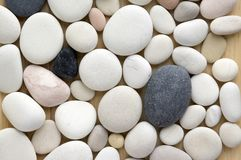 White pebbles background, simplicity, daylight, stones. Mix colors pebbles background, simplicity, daylight, stones, spread on wooden background, one by one Stock Images