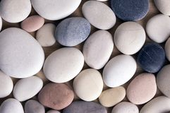 White pebbles background, simplicity, daylight, stones. Mix colors pebbles background, simplicity, daylight, stones, spread on wooden background, one by one Royalty Free Stock Photography