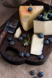 White pecorino cheese and blueberries. Traditional Italian hard cheese and a glass of red wine. Wooden background and dark style stock photos