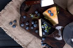 White pecorino cheese and blueberries. Traditional Italian hard cheese and a glass of red wine. Wooden background and dark style royalty free stock photography