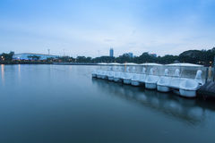 White pedal boat parked in a long line at the dock of the lake. Royalty Free Stock Photography