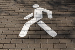 White pedestrian sign on pavement. Stock Image