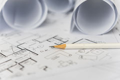 White pencil on architectural for construction drawings. With roll of blueprint royalty free stock photography
