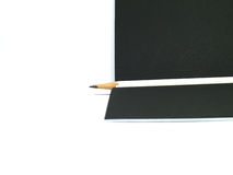 White pencil on black paper. Isolated on white background Royalty Free Stock Photo