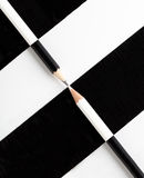 White pencil and black pencil placed on opposite color Stock Photos