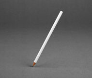 White pencil on a gray background. Stock Photo