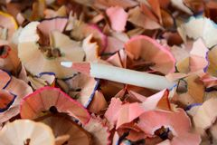 White pencil in middle of color shavings. A white pencil sticking out in the middle of a pile of color pencil shavings Stock Photography
