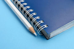 White pencil and spiral of notebook Royalty Free Stock Image