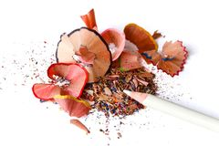 White pencil on top of color shavings and shards with white background. A white pencil laying on top of a pile of shavings and shards from color pencils with Royalty Free Stock Images