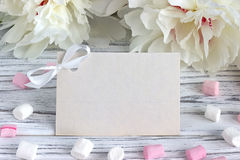 White peonies flowers with empty greeting card on a white wooden background - stock image. Royalty Free Stock Photos