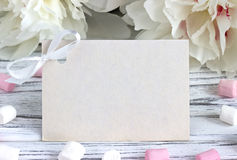 White peonies flowers with empty greeting card on a white wooden background - stock image. Stock Photography