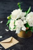White peony flowers bouquet, blank greeting card and craft paper envelope on dark black stone background. Vertical postcard mock u. P. Creative template stock images