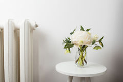 White peony flowers on coffee table in white room interior. Bouquet of white peony flowers on coffee table in white room interior royalty free stock photography