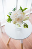 White peony flowers on coffee table in white room interior, brig Stock Image