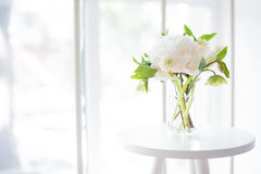 White peony flowers on coffee table in white room interior, brig Royalty Free Stock Photos