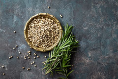 White pepper and fresh rosemary twigs, culinary ingredients on dark background Royalty Free Stock Image