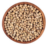 White pepper seeds in a wooden bowl on a white Royalty Free Stock Photos