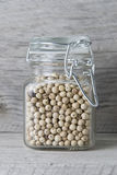 White peppercorns in jar Stock Image