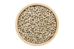 White peppercorns in wooden bowl isolated top view on white. With clipping path stock photo