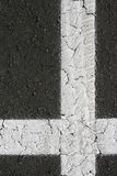 White perpendicular shaped cross on black asphalt. White vertical horizontal shaped perpendicular cross on black asphalt with lite tire tracks. Rubber meets the Royalty Free Stock Image
