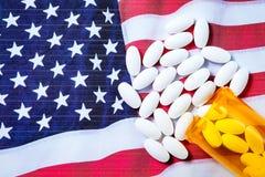 White pharmaceutical pills spilling from prescription bottle over American flag Stock Image