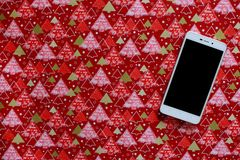 White phone with black empty screen on red festive gift paper with copy space. Christmas and winter holidays background. New year`s tree ornament Royalty Free Stock Photos