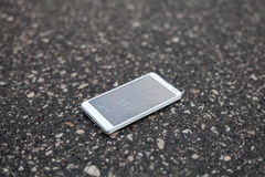 White phone with broken screen. Phone with broken screen lying on the street stock photos